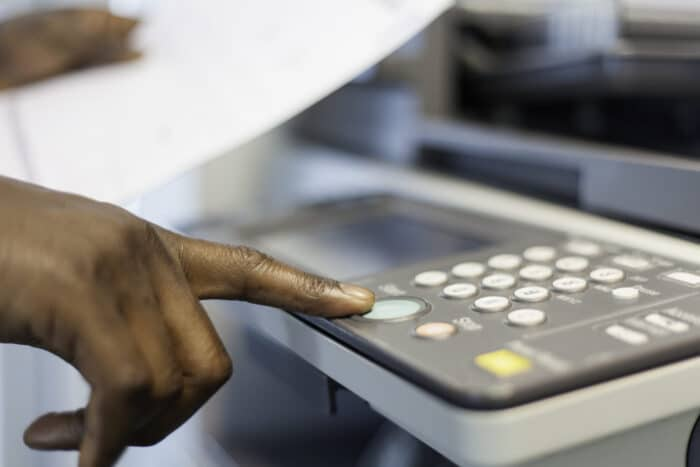 African businessman pressing the start button to print.